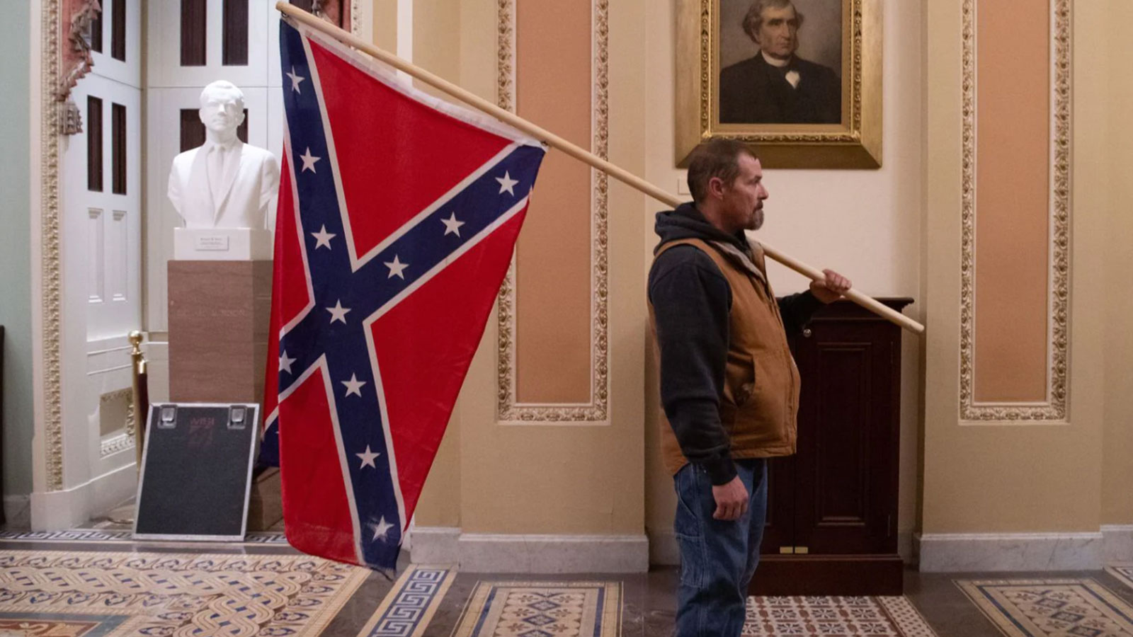 A supporter of then-President Donald Trump holds a Confederate battle flag