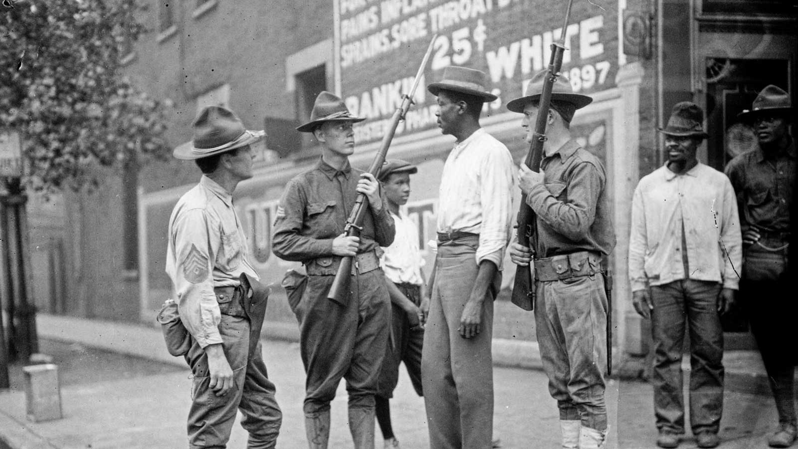 Armed National Guard and African American men standing on a sidewalk during the race riots in Chicago, Illinois, 1919.