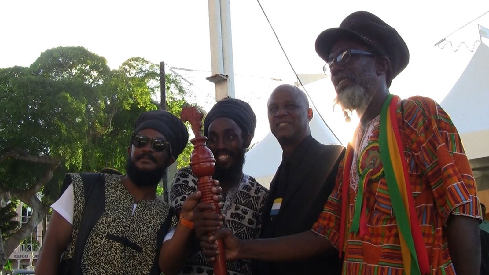 Ras Bongo Wisely Tafari (far right) holds on to the CARICOM's symbol of the reparatory justice movement, the reparations baton, in Castries, Saint Lucia.